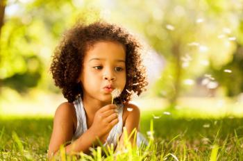 Enfant soufflant fleur